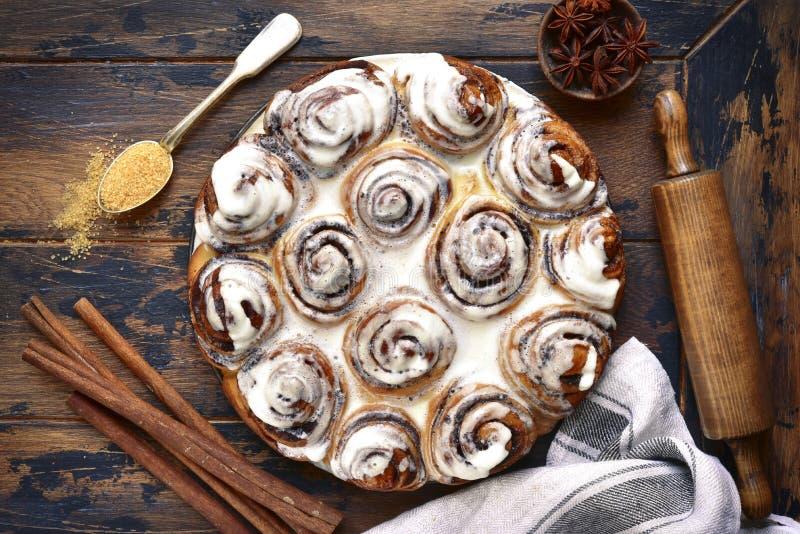 从桂皮卷的自创酵母饼与乳脂状的釉 上面竞争 免版税库存照片