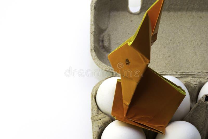 从桔黄色纸的Origami兔子 复活节兔子和白色鸡鸡蛋在箱子,拷贝空间 免版税库存图片