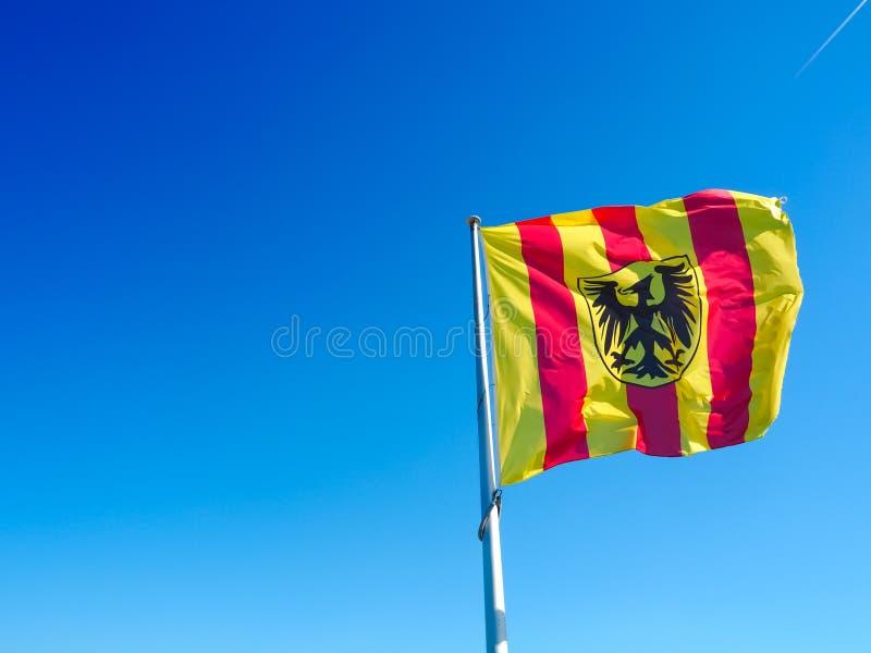 从梅赫伦的自治市的红色和黄色镶边旗子 免版税图库摄影