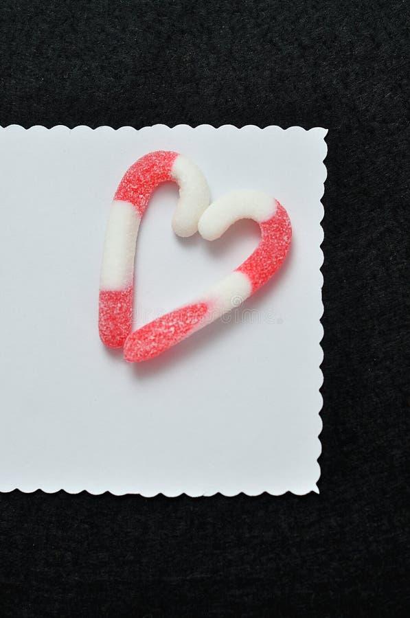 从棒棒糖做的心脏在白色笔记 库存图片