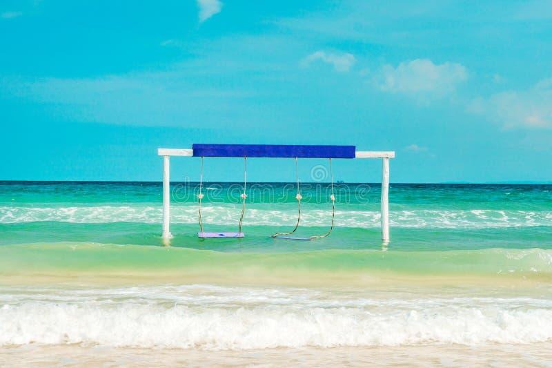 从椰子的摇摆吊在海滩 夏天旅行在普吉岛 白色摇摆在有一个空的题字板的海 免版税库存图片