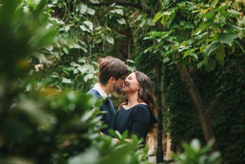 从欧洲的拥抱和亲吻在树之间的学生一对爱恋的年轻美好的夫妇在公园 接近的感觉 免版税库存图片