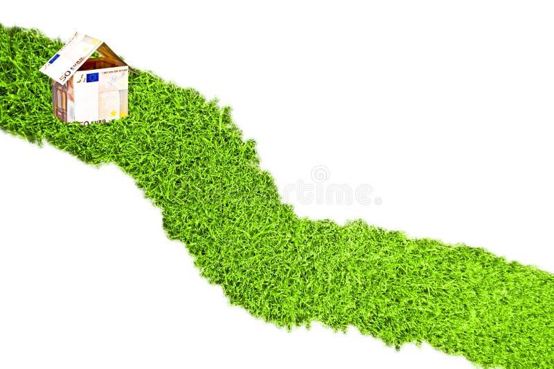 从欧洲货币的一点房子在草路 免版税库存图片