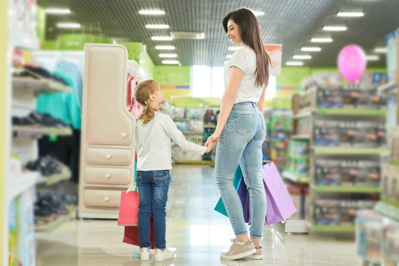 从母亲和女儿购物后面的看法在购物中心的 库存图片