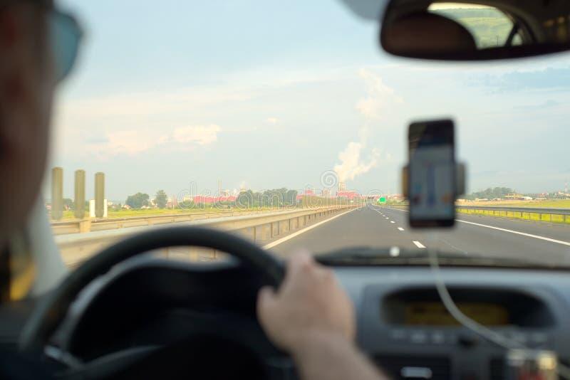 从汽车和工业风景看的路 免版税库存图片