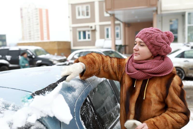 从汽车的妇女刮的雪 库存照片