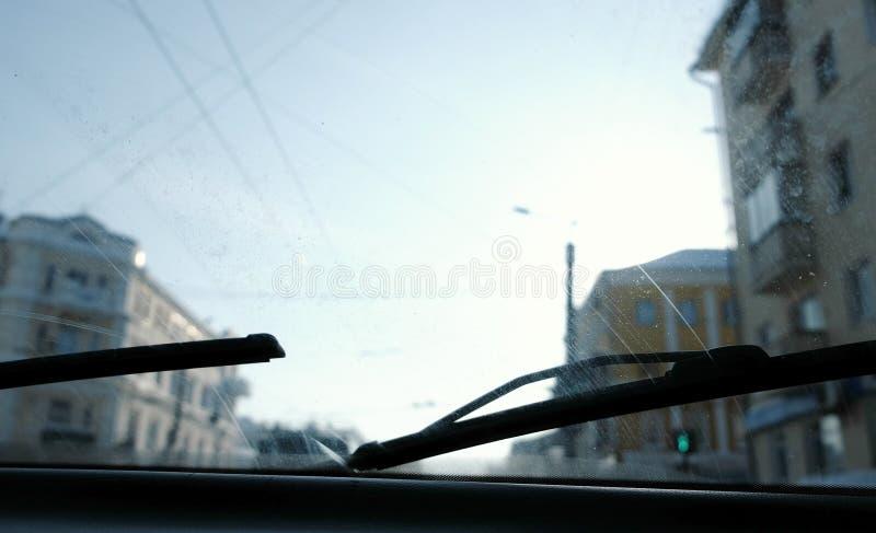 从汽车的看法到城市 在肮脏的挡风玻璃的焦点 风档刮水器经营 免版税库存图片