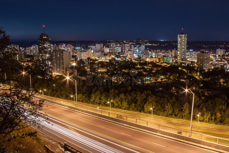 从汽车的街市地平线和光足迹在晚上在哈密尔顿,安大略 免版税库存图片