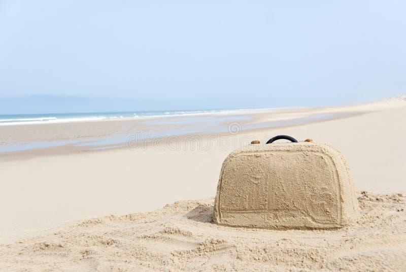 从沙子做的手提箱在海滩 库存照片