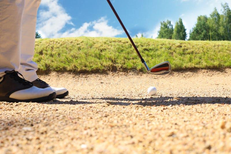从沙子击中从危险的地堡高尔夫球运动员的高尔夫球球击球 免版税图库摄影