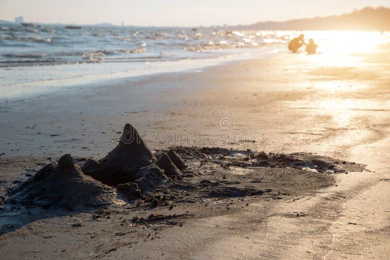 从沙子城堡戏剧的山在海洋海滩 库存图片