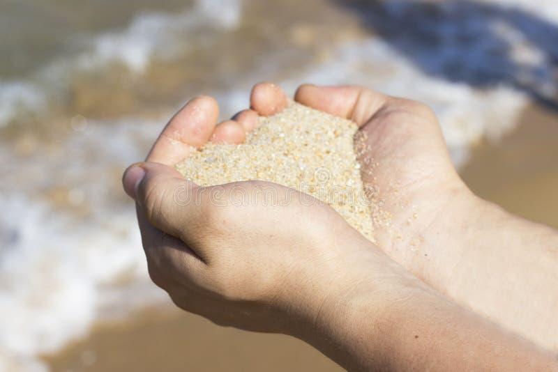 从沙子的心形在以Th为背景的男性手上 免版税图库摄影