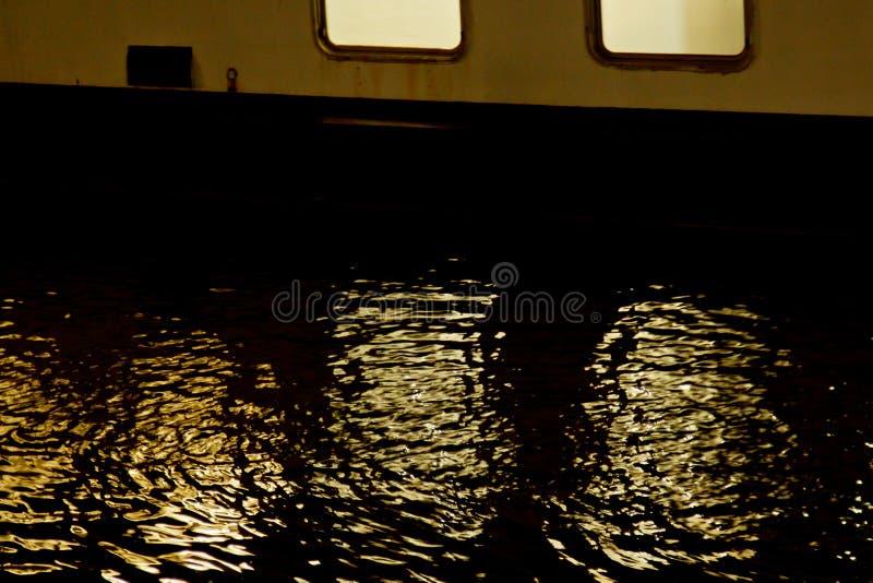 从河船的窗口的光在夜水中被反射 在河的波浪 免版税图库摄影