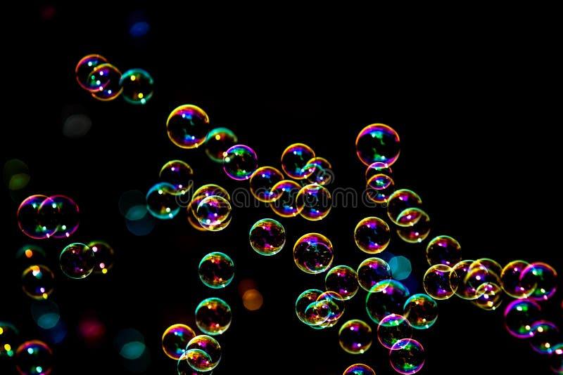从泡影吹风机的肥皂泡在黑暗或黑背景中 图库摄影