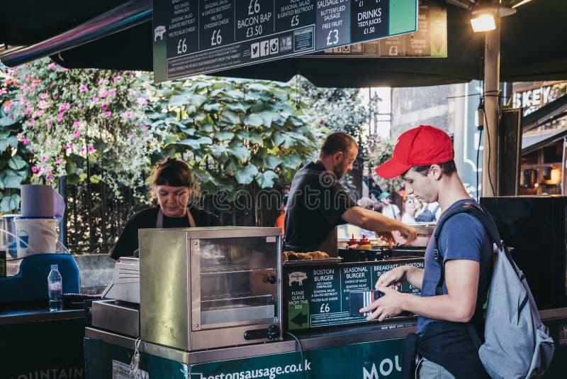从波士顿香肠立场的人预定的食物在自治市镇市场,伦敦,英国上 免版税库存照片