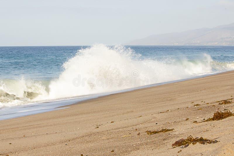 从波浪的大爆炸的飞溅的浪花在沙滩,与开放海洋浩瀚 免版税库存图片