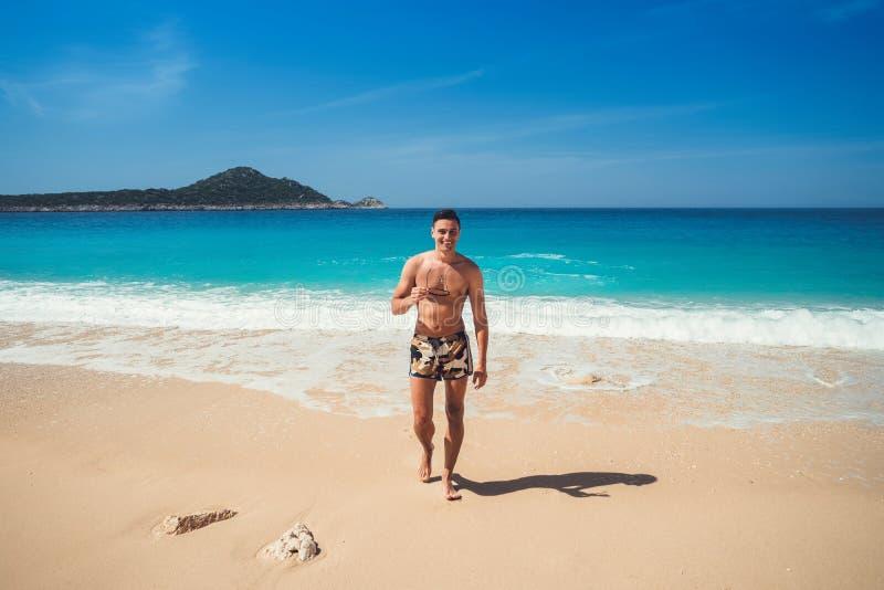 从海出来的一个年轻人在游泳以后 v的愉快的人 库存照片