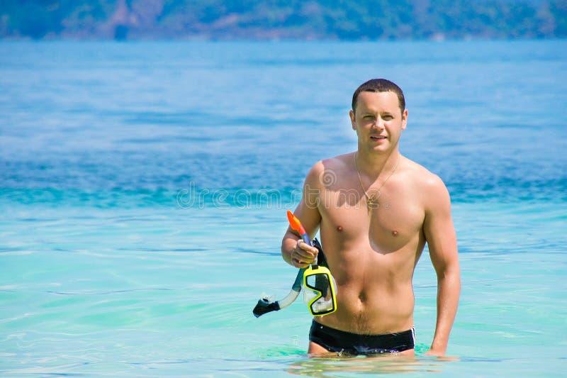从海出来的年轻人在游泳以后 愉快的人在度假 一个人走海滨 库存图片