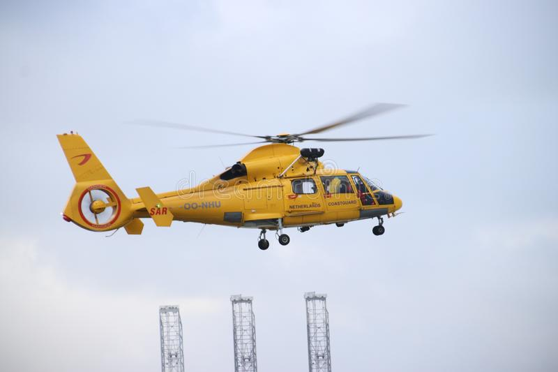 从海岸警备队的OO-NHU直升机在荷兰在腐烂口岸的Europoort港口把行动的平台留在  免版税库存照片