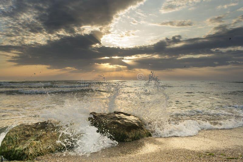 从海的日出,有巨大太阳颜色的,晃动与波浪和剧烈的云彩在天空在风景视图 库存照片