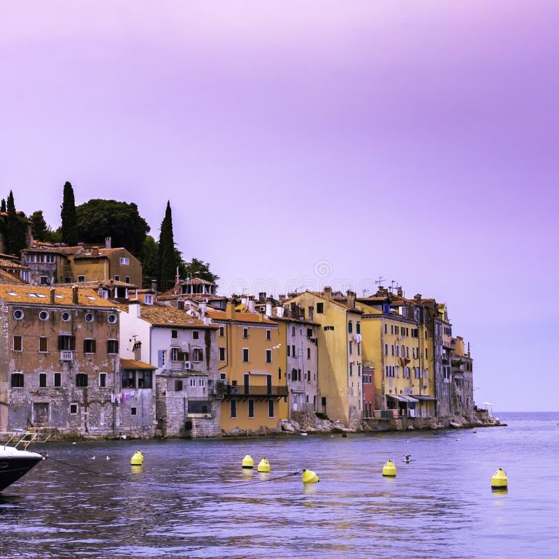 从海的看法罗维尼老镇的海岸的有五颜六色的房子的日落的,克罗地亚 库存照片