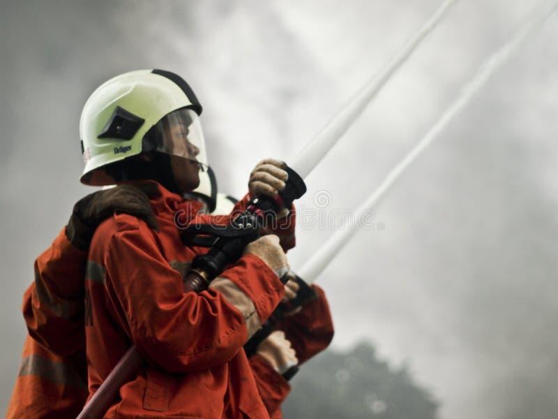 从消防队员的水枪射击 免版税库存图片