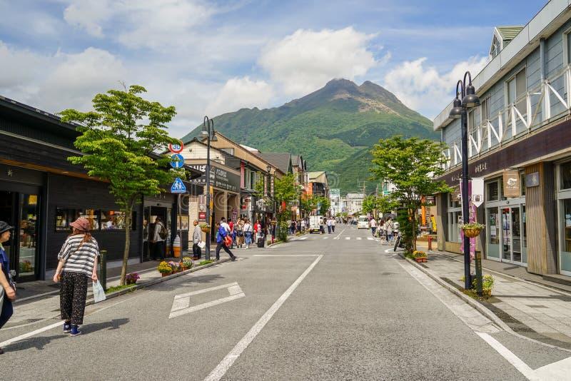 从火车站的主路充满人,街景画和地方商店指挥对新鲜的绿色Yufudake山峰和蓝色 免版税库存照片