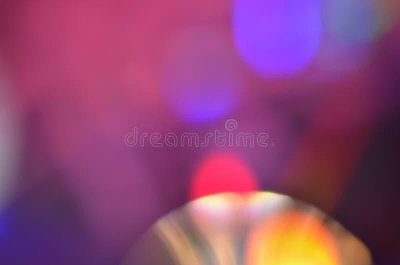 从灯光接受的抽象五颜六色的bokeh背景在CD的盘的与闪烁, defocused 库存照片