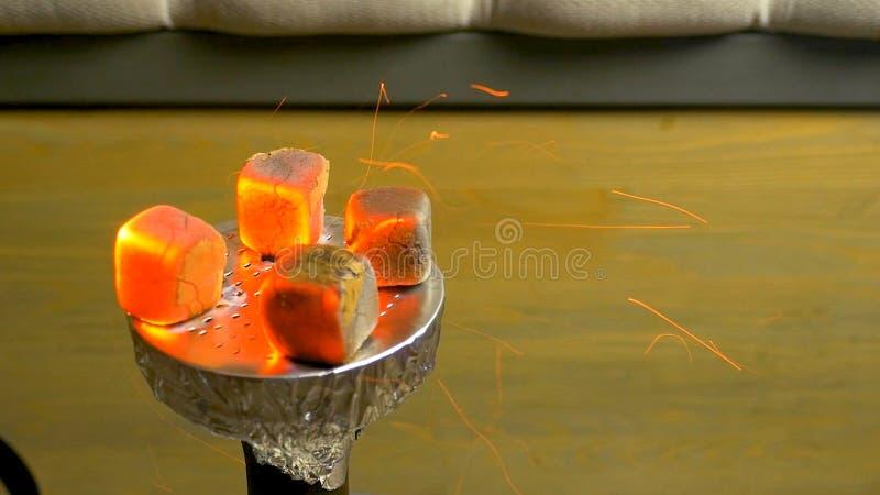 从灼烧的煤炭水烟筒的火花 在碗的水烟筒烟草 燃烧的红椰子木炭 亦称准备shisha, 库存照片