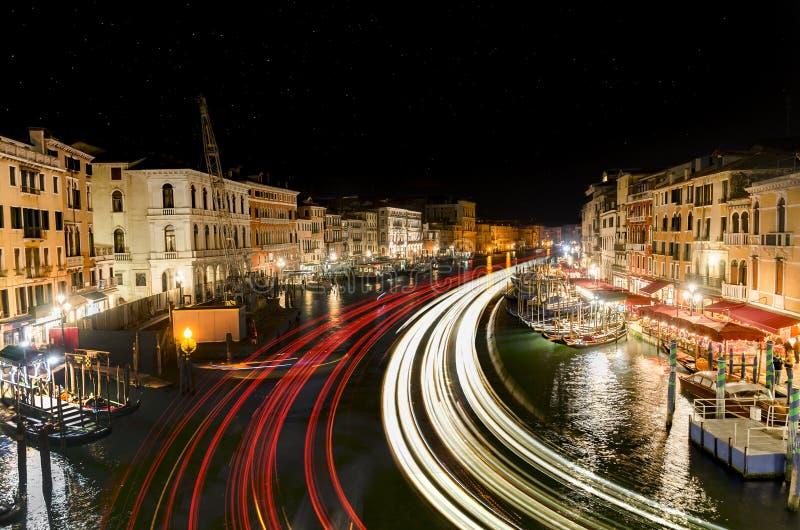 从点燃在大运河,威尼斯的足迹的Rialto桥梁的夜视图 免版税库存照片