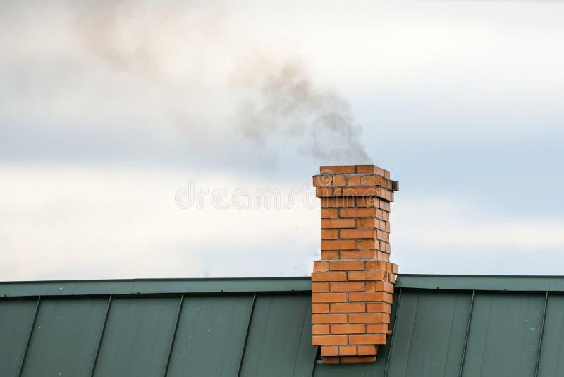从烟囱的烟,热化 ?? 从房子烟囱出来反对天空蔚蓝背景 免版税库存图片