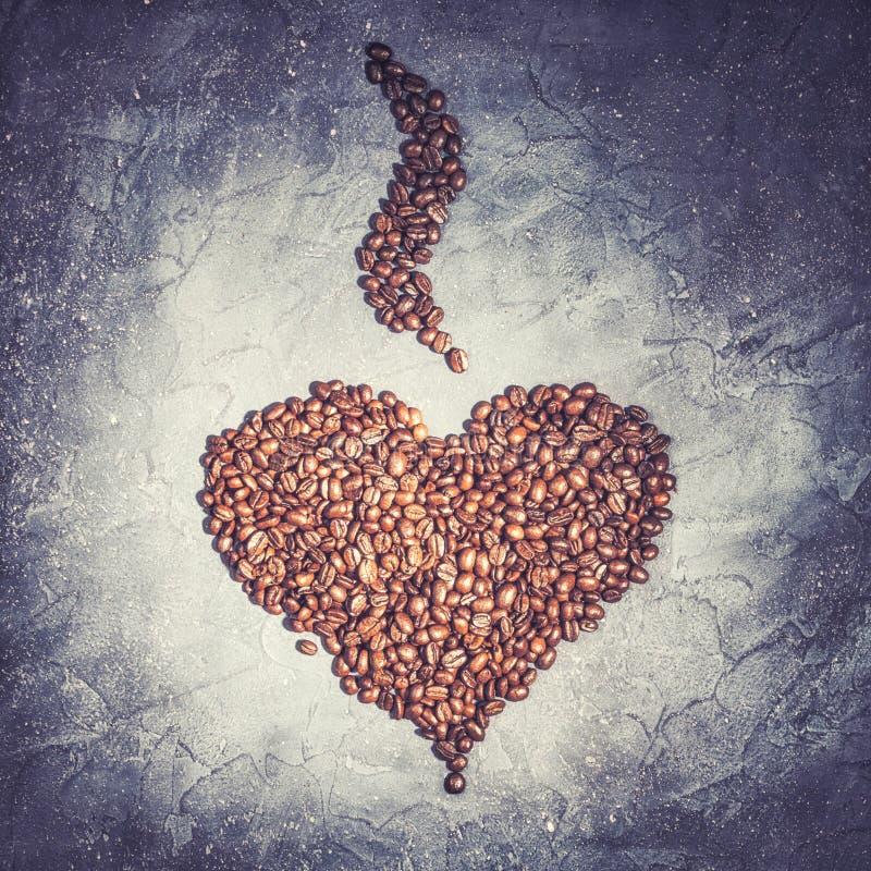 从烤咖啡豆的心脏形状与在紫罗兰色石背景的蒸汽 库存图片