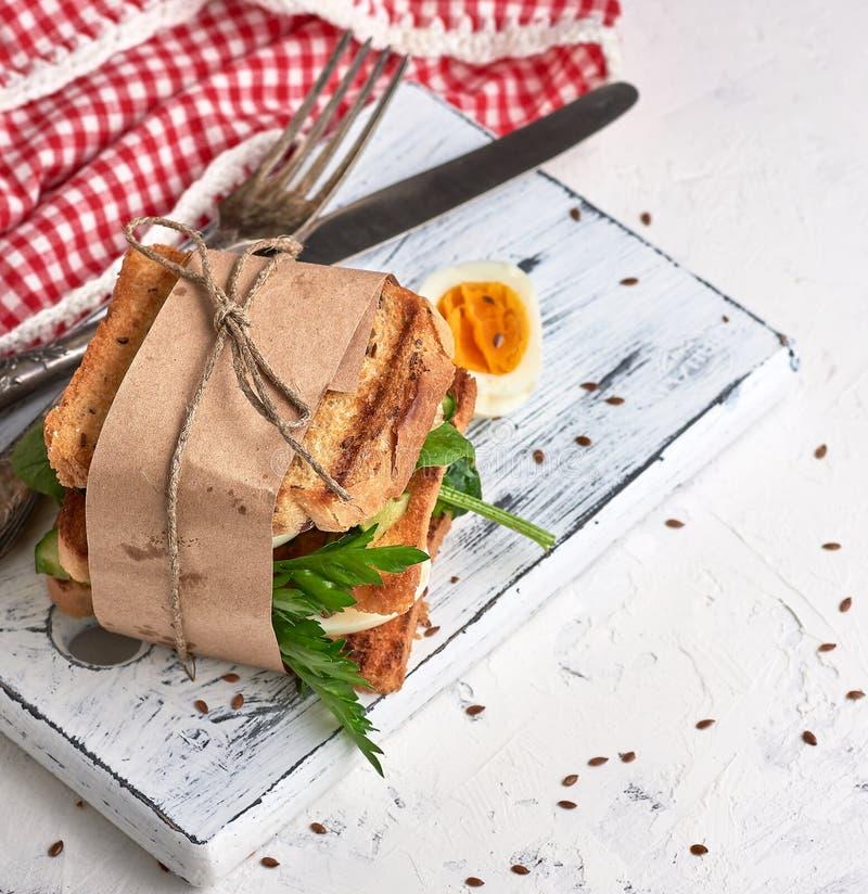从烤面包片、菜和熟蛋方形的片断的三明治  库存照片