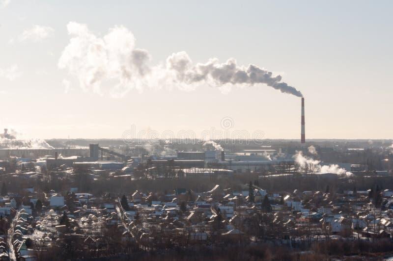 从热电驻地管子抽烟反对天空 环境的污染在城市 图库摄影