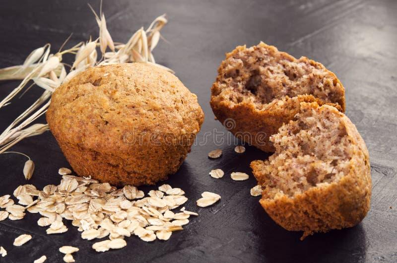 从燕麦面粉、燕麦粥和麦子耳朵的自创蛋糕在黑暗的背景 库存图片