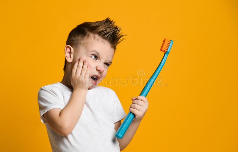 从牙痛-牙齿问题的小男孩痛苦 库存照片