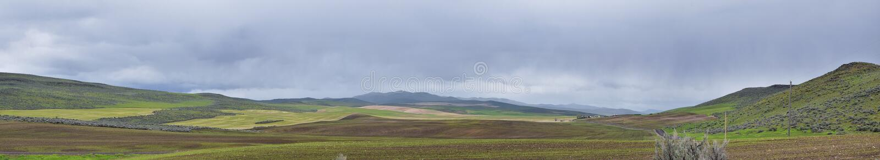 从犹他和爱达荷的边界的风景风雨如磐的全景视图从跨境84,I-84、看法农村种田与绵羊和co 免版税库存照片