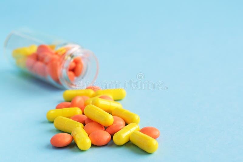 从玻璃瓶的黄色和橙色胶囊在蓝色背景 o 流行病,止痛药,医疗保健,治疗 免版税库存照片