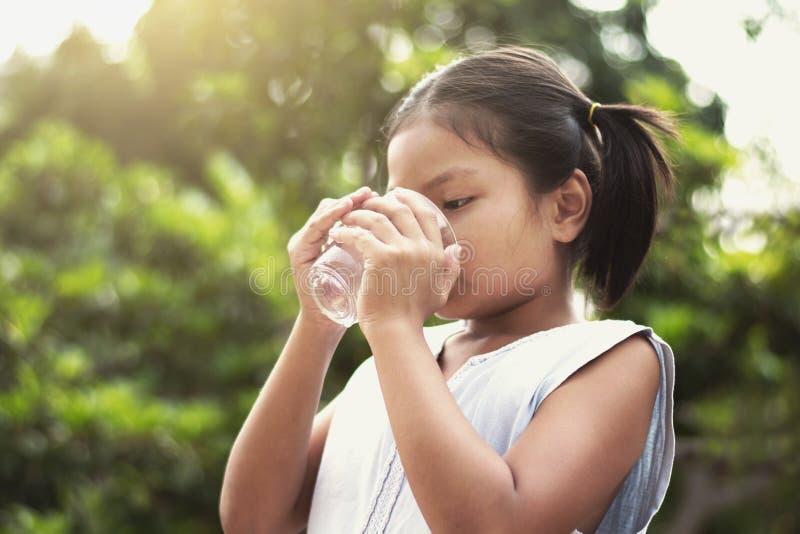 从玻璃的亚洲小女孩饮用水与阳光backgr 库存图片