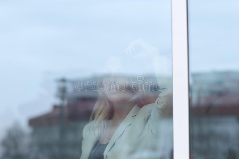 从玻璃的后面 看办公室窗口的年轻女商人 免版税库存图片
