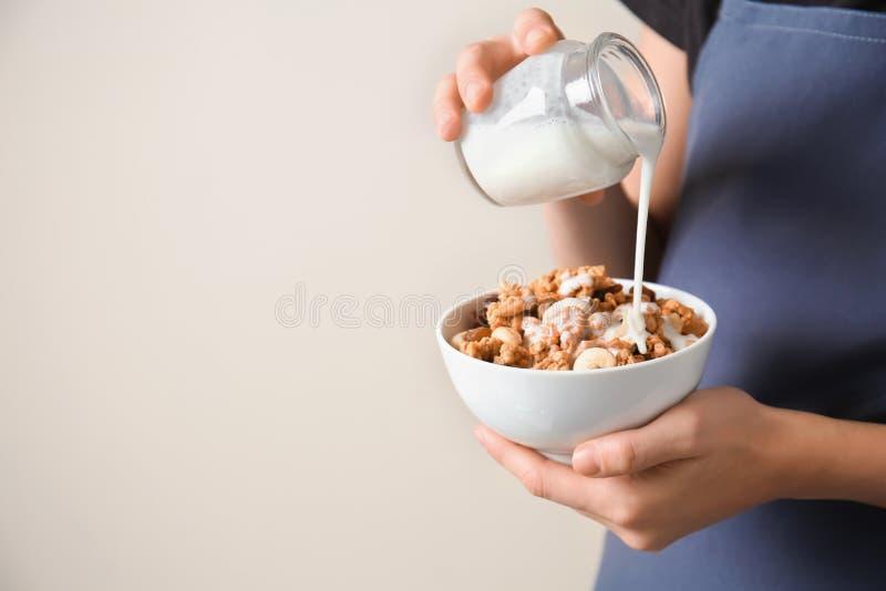 从瓶子的妇女倾吐的牛奶到有格兰诺拉麦片的碗里在轻的背景 免版税库存照片
