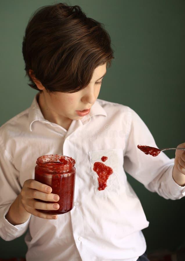 从瓶子的少年不整洁男孩下落果酱到白色衬衣做肮脏的斑点 库存图片