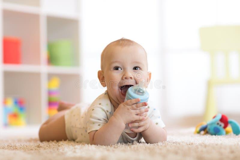 从瓶的俏丽的男婴饮用水 微笑的孩子是7个月 免版税库存照片