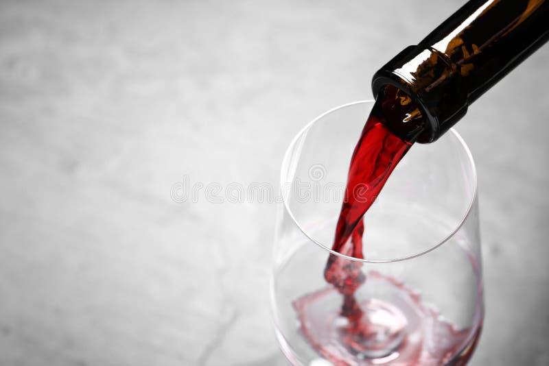 从瓶的倾吐的红酒到在轻的背景,特写镜头的玻璃里 免版税库存照片