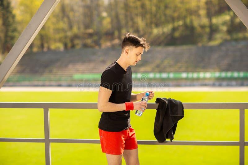 从瓶的健身人饮用水 渴运动员有冷的茶点饮料在强烈的锻炼以后 免版税库存照片