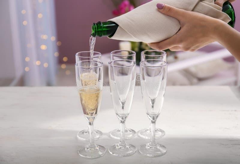 从瓶的妇女倾吐的香槟到在白色桌上的玻璃里 免版税库存图片