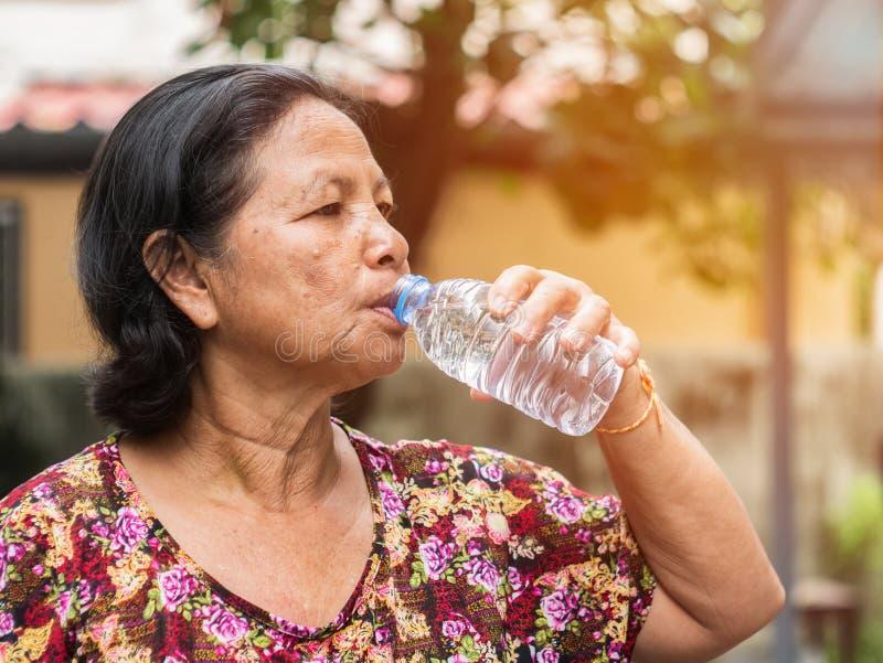 从瓶的年长亚裔妇女饮用水 免版税图库摄影