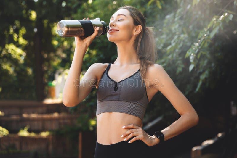 从瓶的微笑的年轻健身女孩饮用水 免版税库存照片
