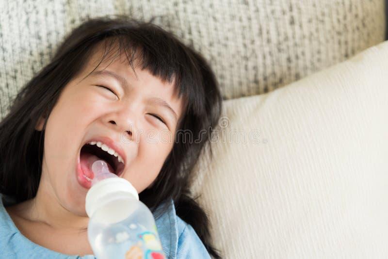 从瓶的愉快的逗人喜爱的小女孩饮用水在沙发 免版税库存照片