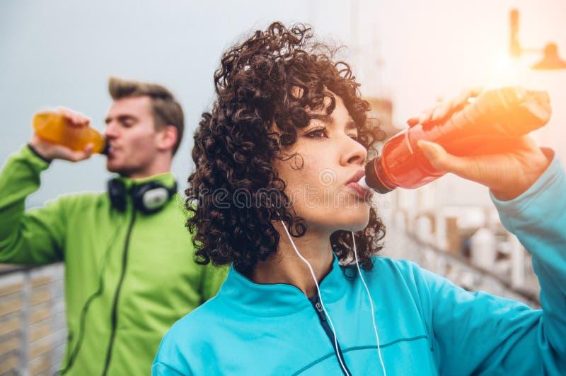 从瓶的男人和妇女饮用的能量饮料在健身体育锻炼以后 免版税库存照片